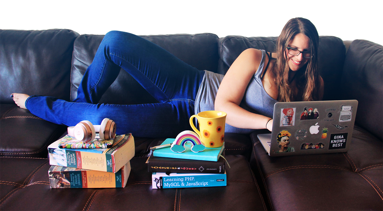 a photo of a woman with brown hair and glasses wearing jeans and a grey tank top lying on a brown leather couch with a laptop covered in stickers in front of her. Also on the couch in front of her are stacks of books topped with a pair of headphones and an eraser shaped like a rainbow.